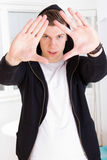 Urban trendy guy wearing hood framing his face with hands Stock Photography