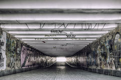 Urban underground tunnel with modern graffiti. Old underground tunnel with modern creative graffiti royalty free stock images
