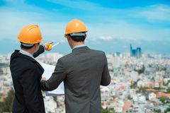 Urban view. Businessmen in hardhats taking a look at the blueprint in urban environment royalty free stock photo