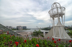 Urban view. Flowers, lake, buildings and contemporary style monument Royalty Free Stock Images