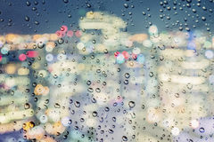 Urban view of rain drops falls on a window during a stormy day Stock Photo