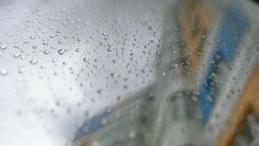 Urban view of rain drops falls on a window during a stormy day overlooking city skyline in the background.  stock video