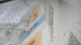 Urban view of rain drops falls on a window during a stormy day overlooking city skyline in the background.  stock footage