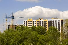 Urban view of silhouettes of two high industrial tower cranes above green tree tops working at construction of new brick building stock photo