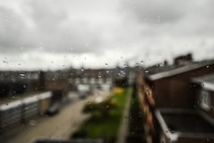 An urban view of a street and buildings seen through the wet raindropped window glass, IJmuiden, Holland. An urban view of a street with its buildings seen Royalty Free Stock Image