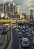 An urban view with a train and a busy road Stock Photos