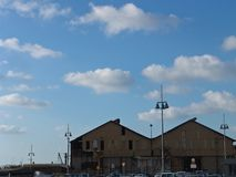 Urban view of two roof tops of big buildings by the sea port, boat houses with tall city lamps in front, under cloudy sky royalty free stock images