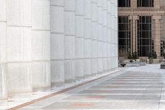 Urban walkway and columns moving to perspective between office buildings stock photo