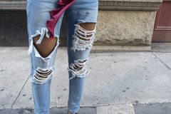 African american woman`s legs with ripped blue jeans city side w stock photography