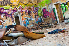 Urban War Zone. Abandoned courtyard full of household leftovers and graffiti walls Royalty Free Stock Images