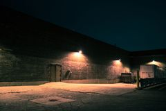Urban warehouse building at night Stock Images