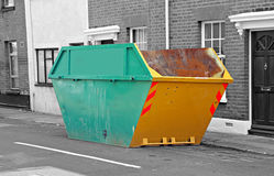 Urban waste skip. Photo of a large urban waste disposal skip outside row of town houses Royalty Free Stock Image