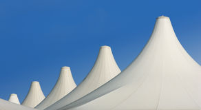 Urban white dune. Urban architecture: white roofs of tents aligned over blue sky Royalty Free Stock Photos