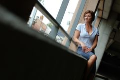 Urban Woman. Mature urban woman sitting down stock image