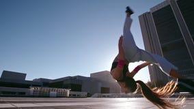 Urban Woman doing frontflip outdoors. Woman doing frontflip outdoors in city. Urban female in action practicing parkour and flashkick stock video