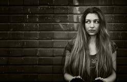 Urban woman and grunge wall. Urban young woman sitting near grungy brick wall royalty free stock photography
