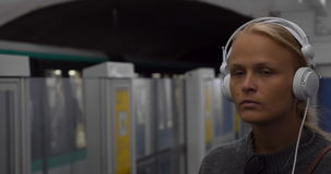 Urban woman listening to music in underground. Young blond woman with sad look listening to music in headphones at subway station, trains passing by stock video