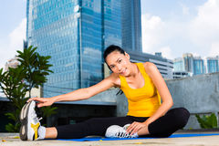 Urban woman sports - fitness in Asian city. Urban sports - Asian Indonesian woman doing fitness in the city on a beautiful summer day stretching before running Royalty Free Stock Image