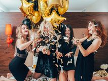 Urban women glamor luxury lifestyle celebration. Urban women. Glamor and luxury lifestyle. Celebration. Row of cheerful young females relaxing on bed. Hotel room royalty free stock images