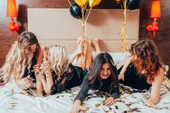 Urban women glamor luxury lifestyle celebration. Urban women. Glamor and luxury lifestyle. Celebration. Row of cheerful young females lying on bed. Hotel room stock image