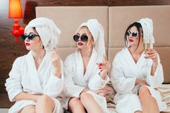 Urban women luxury arrogance bathrobes champagne. Urban women luxury. Arrogance and skepticism. Champagne relaxation leisure. Sunglasses, bathrobes and turbans royalty free stock image