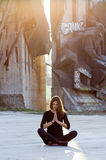 Urban yoga. Young woman performing yoga or meditation in outdoor urban setting Royalty Free Stock Image