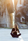 Urban yoga. Young woman performing yoga or meditation in outdoor urban setting Royalty Free Stock Photos