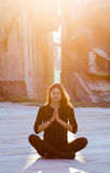 Urban yoga. Young woman performing yoga or meditation in outdoor urban setting Stock Photos