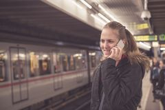 Young female making a call with smartphone at subway station stock photo