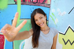 Urban young girl showing v peace sign in city. Cool Asian woman leaning on graffiti background at the Berlin wall, Germany. Modern portrait Stock Photos