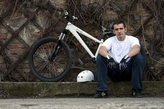 Urban young male bike rider 3. Urban street bike rider sitting royalty free stock photo