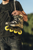 Urban young man holding his skates on the shoulder Stock Image