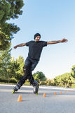 Urban young man on roller skates on the road at summer time royalty free stock photos