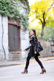 Urban young woman walking in leather jacket city stock images