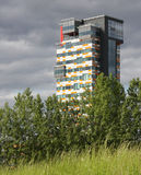 Urbanisation. Modern skyscraper appearing behind meadows and trees. Symbol for urbanisation stock photos
