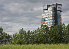 Urbanisation. Modern skyscraper appearing behind meadows and trees. Symbol for urbanisation Royalty Free Stock Image
