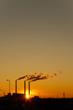 Urbanistic decline. Sunset for industrial buildings with smoking pipes royalty free stock images