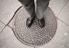 Urbanite man standing on sewer manhole Royalty Free Stock Images