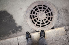 Urbanite man stands near rusty sewer manhole Royalty Free Stock Image