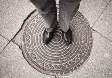 Urbanitemann, der auf Abwasserkanaleinsteigeloch steht Lizenzfreie Stockbilder