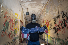 Urbex explorer finding a burned up flag. A man with a gas mask explores an abandoned building finding a burned up flag Stock Images
