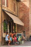 Urbino, Italy - August 9, 2017: the family has had a snack at the ice cream parlor. Urbino, Italy - August 9, 2017: the family has had a snack at the ice cream Royalty Free Stock Image
