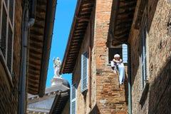 Urbino Włochy, Sierpień, - 9, 2017: starszy kobiety obwieszenie odziewa w okno drugie piętro Zdjęcie Royalty Free