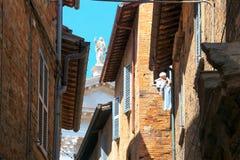 Urbino Włochy, Sierpień, - 9, 2017: starszy kobiety obwieszenie odziewa w okno drugie piętro Przez Federico Veterani Fotografia Royalty Free