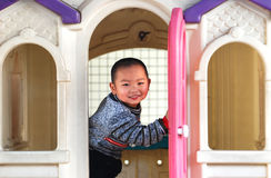 An urchin and doll house. A naught Chinese boy Play in the colorful plastic doll house smiling Stock Photos