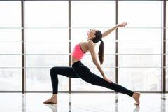 Urdhva Virabhardasana Woman practicing advanced yoga in studio room Stock Images