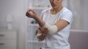 Urdidura elástica de aplicação fêmea do cotovelo após a ortopedia e os cuidados médicos do traumatismo do esporte vídeos de arquivo