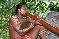 Ureinwohnerschauspieler führt Musik mit traditionelles didgeridoo Musikinstrument im Tjapukai-Kultur-Park in Kuranda, Queensland  lizenzfreie stockfotos