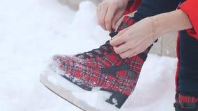 Uren en landschap Een vrouw verbond haar schoenveters op heldere rode ijs het schaatsen schoenen stock videobeelden