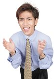 Urgent business appeal. Oriental young businessman with alarmed and urgent facial expression leaning forward with a begging and startled hands gesture. Isolated Stock Images